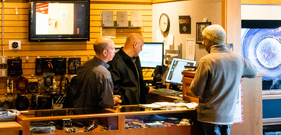 Two of Stereo Planet's AV installation experts consult with a client, who is standing at the front counter